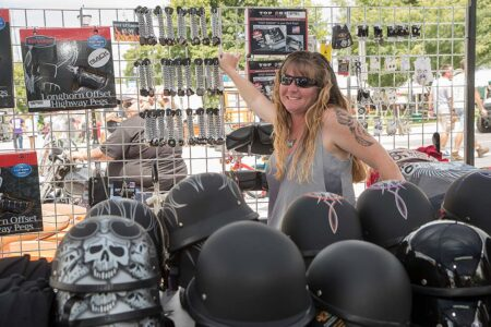 lady with long blonde hair stands surrounded by motorcycle helmets and accessories