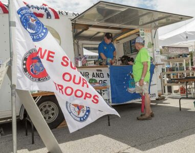 two men chat at a vendor trailer honoring the military