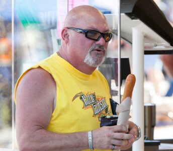 bald man with sleevless tee shirt holding large corn dog