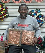 photo of jim carr showing off two metal art pieces