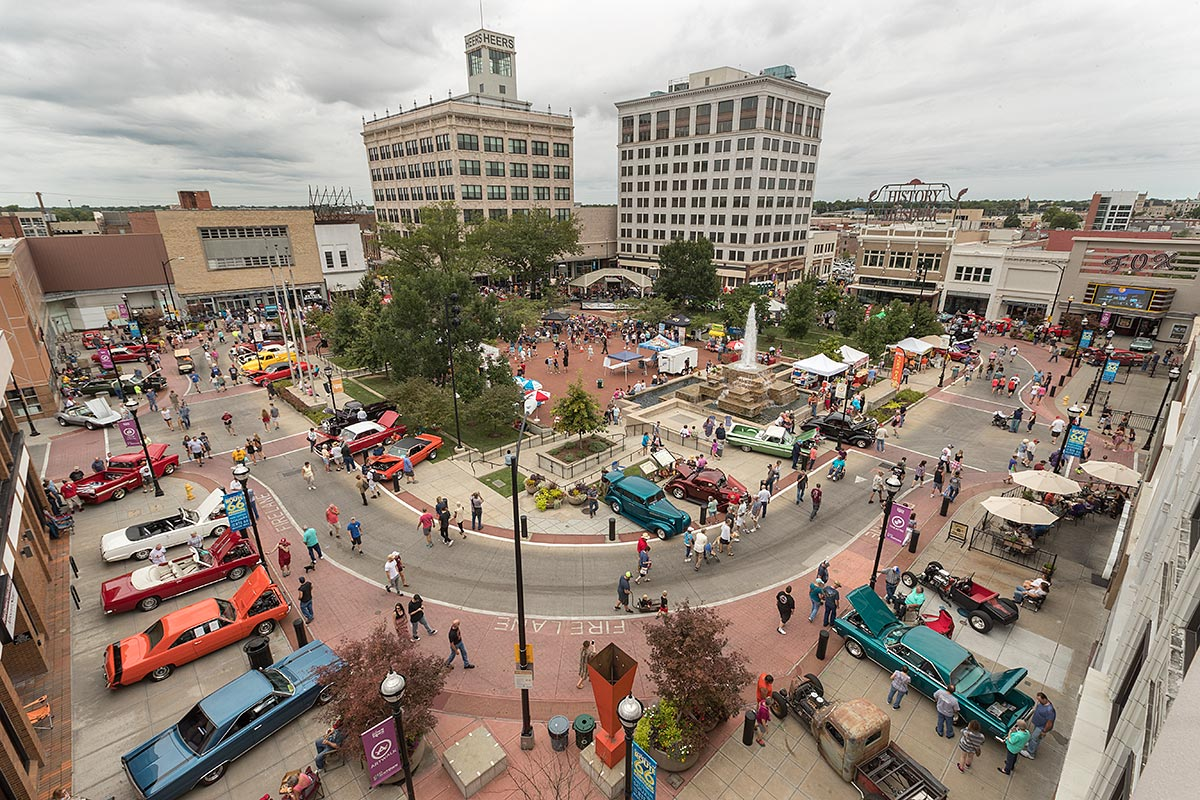 wide aerial photo of park central square with many classic cars and people