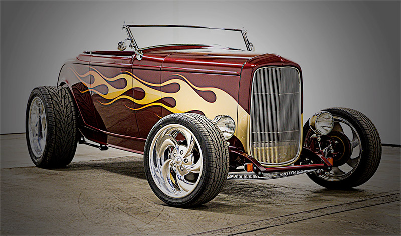 photo of maroon 1932 ford roadster with yellow flames painted on the side